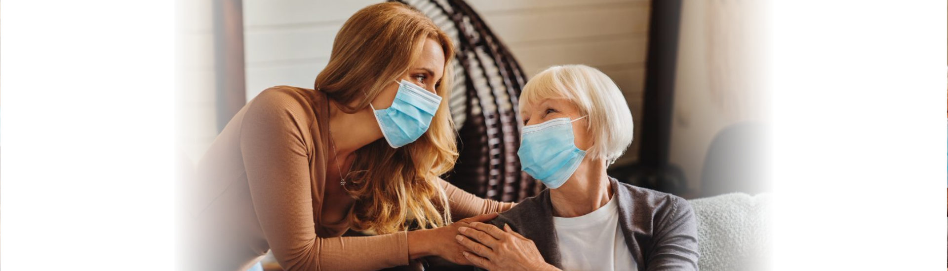 caregiver and elderly woman wearing face mask